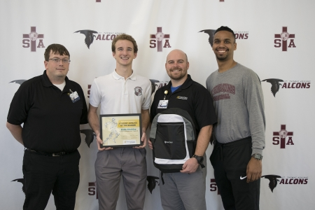 Kade Bleakley with, from left, North Oaks Sports Medicine Athletic Trainer Jeremy Kulbeth and Head Athletic Trainer/Supervisor Matthew Rabalais, and Falcons Head Basketball Coach Raymone Andrews